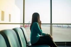 Aziatische vrouwenpassagier gebruikend smartphone en controlerend vlucht of online controle en reisontwerper bij internationale l stock foto