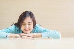Aziatische vrouwenslaap door gelogen op bureau met gelukkig gezicht in rusttijd van lezingsboek op vage houten bureau en muur gew Stock Foto
