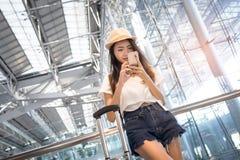 Aziatische vrouwentiener die smartphone gebruiken bij luchthaven Stock Foto's