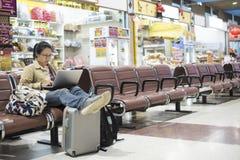 Aziatische vrouwentiener die smartphone gebruiken bij luchthaven eindsittin royalty-vrije stock foto