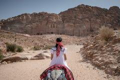 Aziatische vrouwentoerist het berijden ezel in Petra, Jordani royalty-vrije stock fotografie