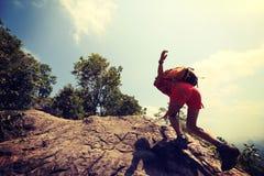 Aziatische vrouwenwandelaar die rots op berg piekklip beklimmen Royalty-vrije Stock Foto