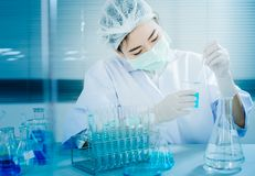 Aziatische vrouwenwetenschapper die met reageerbuis onderzoek naar klinisch laboratorium maken Royalty-vrije Stock Fotografie