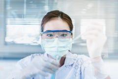 Aziatische vrouwenwetenschapper die met reageerbuis onderzoek naar klinisch laboratorium maken stock afbeeldingen