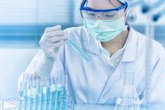 Aziatische vrouwenwetenschapper die met reageerbuis onderzoek naar klinisch laboratorium maken De wetenschap, de chemie, de techn royalty-vrije stock fotografie
