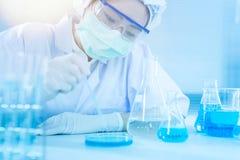Aziatische vrouwenwetenschapper die met reageerbuis onderzoek naar klinisch laboratorium maken De wetenschap, de chemie, de techn Stock Afbeelding