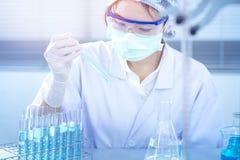 Aziatische vrouwenwetenschapper die met reageerbuis onderzoek naar klinisch laboratorium maken De wetenschap, de chemie, de techn Royalty-vrije Stock Afbeelding