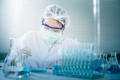 Aziatische vrouwenwetenschapper die met reageerbuis onderzoek naar klinisch laboratorium maken De wetenschap, de chemie, de techn Royalty-vrije Stock Afbeeldingen