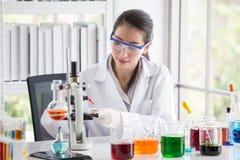 Aziatische vrouwenwetenschapper Research en Reactievrouw die een vloeistof in een buis in Laboratorium, de geneeskundechemie giet stock foto's