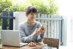 Aziatische vrouwenzitting bij een lijst en thuis het gebruiken van smartphone Type Stock Foto