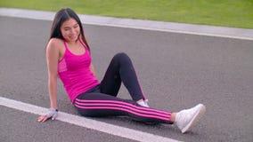Aziatische vrouwenzitting op asfaltweg na geschiktheid opleiding Het gelukkige vrouw glimlachen stock video
