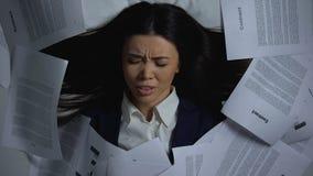 Aziatische werknemer die omvatten met documenten, die van werkbelasting, doorsmelting worden gewanhoopt stock footage