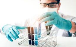 Aziatische wetenschappelijke onderzoeker of arts die reageerbuis in arbeid kijken stock afbeeldingen
