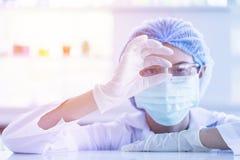 Aziatische wetenschapper die kleine geneeskundecapsule houden stock afbeeldingen