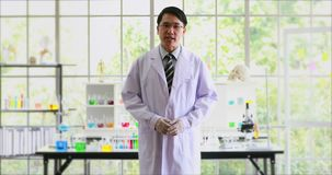 Aziatische wetenschapper die zijn laboratorium introduceert aan de camera stock videobeelden