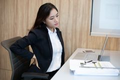 Aziatische Zakenlieden die hard werken tot zij rugpijn hebben stock afbeeldingen