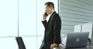 Aziatische zakenman die cellphone in bureau gebruiken stock videobeelden