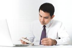 Aziatische zakenman die ernstig in het bureau met mede laptop werken Stock Afbeeldingen
