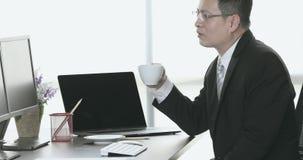 Aziatische zakenman die hete koffie van witte kop in zijn bureau drinken stock video