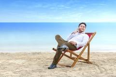 Aziatische zakenman die op mobiele telefoon spreken terwijl helling terug in de ligstoel op strand royalty-vrije stock foto