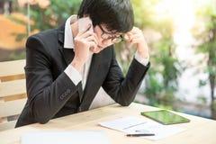 Aziatische zakenman die telefoon met behulp van die rapport bekijken stock afbeelding