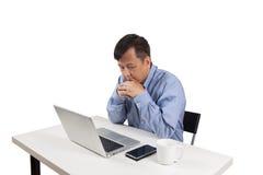 Aziatische zakenman die zijn laptop met hand lezen onder zijn kin Stock Afbeeldingen
