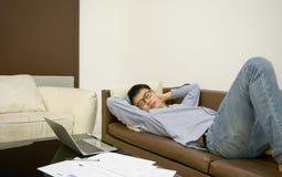 Aziatische zakenmanslaap op bank in woonkamer bij nacht stock foto's