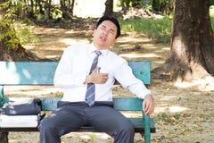 Aziatische zakenmanzitting in een park Borstpijn en hartaanval Stock Afbeeldingen