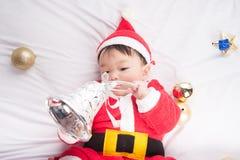Aziatische Zuigelingsbaby in Kerstmisviering van het santakostuum op wit Stock Afbeeldingen