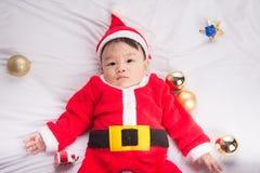Aziatische Zuigelingsbaby in Kerstmisviering van het santakostuum op wit Stock Foto