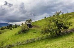 Azienda agricola della montagna con la vecchia casa di legno vicino a crusca, la Transilvania, Fotografia Stock Libera da Diritti