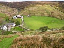 Azienda agricola a distanza della collina, Inghilterra Fotografia Stock