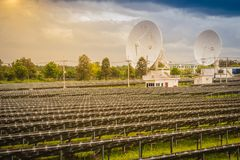 Azienda agricola solare della larga scala con i riflettori parabolici sotto drammatico Immagine Stock