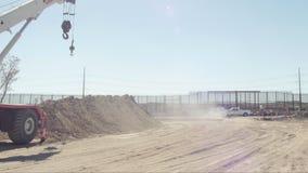 Azionamenti del camion attraverso il cantiere vicino al confine archivi video