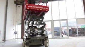 Azionamenti idraulici della piattaforma elevatrice di forbici in un magazzino archivi video