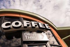 Azionamento del caffè attraverso il segno con il cielo nuvoloso Immagini Stock
