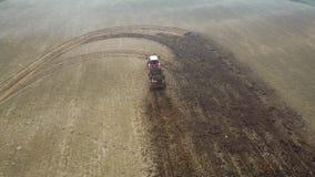 Azionamento del trattore agricolo through il campo agricolo e fertilizzandolo con concime stock footage