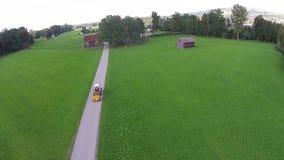 Azionamento del trattore durante un giorno soleggiato del prato di verde del campo archivi video