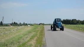Azionamento del trattore sul giacimento rurale di agricoltura e della strada delle balle della paglia video d archivio