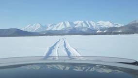 Azionamento dell'automobile sulla strada del ghiaccio sopra il lago stock footage
