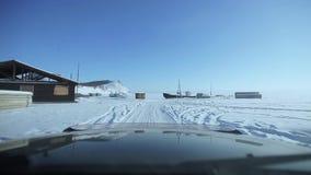 Azionamento dell'automobile sulla strada del ghiaccio sopra il lago archivi video