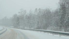 Azionamento delle automobili attraverso Forest In Snowstorm Vista tramite il parabrezza Movimento lento stock footage