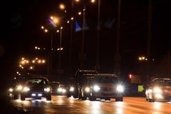 Azionamento delle automobili sulla strada principale nella notte immagine stock