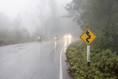 Azionamento di veicolo sulla strada curva in nebbia pesante Fotografia Stock Libera da Diritti