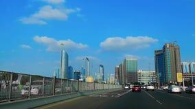 Azionamento in strada del corniche della città di Abu Dhabi con la vista delle torri famose contro cielo blu e le nuvole video d archivio