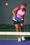 Azione di Pickleball - donna senior che colpisce Pickleball Fotografia Stock