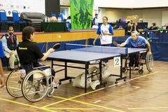 Azione di ping-pong della sedia a rotelle degli uomini Immagini Stock