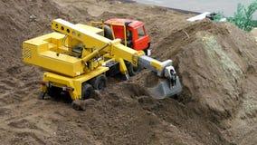 Azione di scavatura del macchinario scavatore dell'escavatore nel cantiere archivi video