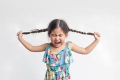 Azione divertente del gioco asiatico della ragazza con i suoi capelli del cavallino Fotografia Stock