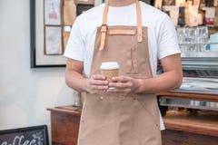Azja barista kelnera odzieży fartuch trzyma gorącym bierze oddaloną filiżankę obrazy stock
